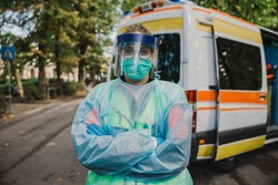 Portrait of a female doctor nurse in front of the ambulance with protective suit, gloves, mask and visor against the infection of Coronavirus, Covid-19 during her shift of service to the community