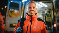 Portrait of a Female EMS Paramedic Proudly Standing in Front of Camera in High Visibility Medical Orange Uniform with