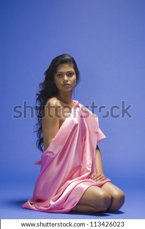Portrait of a female fashion model posing against blue background