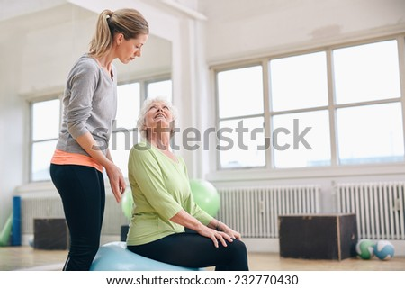 Portrait of a female gym instructor helping an older woman. Portrait of female coach assisting senior woman exercising in health club.