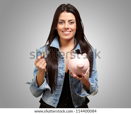 Portrait Of A Female Holding A Coin And Piggy bank On A Gray Background
