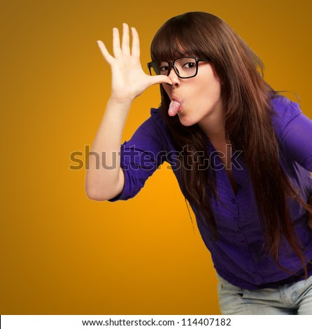 Portrait of a female making funny face on yellow background
