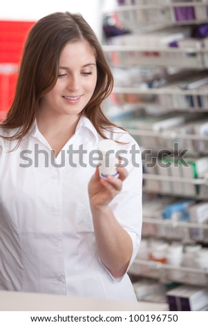 Portrait Of A Female Pharmacist At Pharmacy Reading Information On Medicine.
