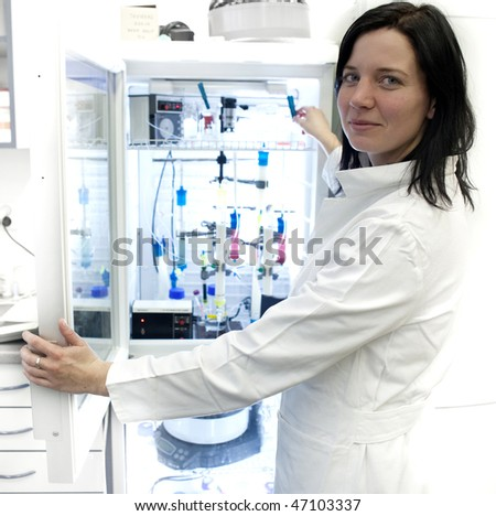 Portrait of a female researcher carrying out research experiments in a lab - researcher taking a substance from a freezer