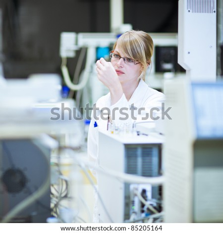 portrait of a female researcher/chemistry student carrying out research in a chemistry lab (color toned image; shallow DOF)