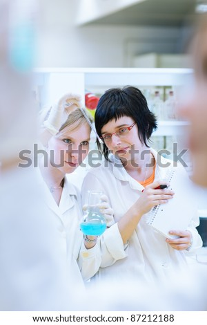 portrait of a female researchers/chemistry students carrying out research in a chemistry lab (color toned image; shallow DOF) - stock photo