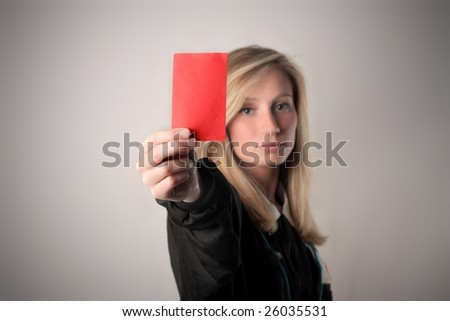 portrait of a female soccer referee showing a red card (focus on card)