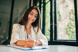 Portrait of a female student filling questionnaire while sitting at desk at university.