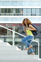 Portrait of a female student walking up stairs to college