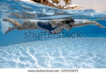 Portrait of a female swimmer, that jumping and diving into swimming pool. Sporty woman.Low angle view from the swimming pool. #529243693
