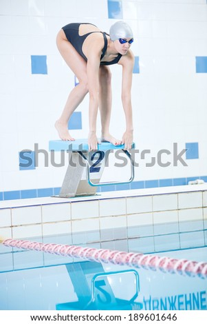 Portrait of a female swimmer, that wearing a swimming cap and goggles and preparing to jump into swimming pool. Sporty woman.