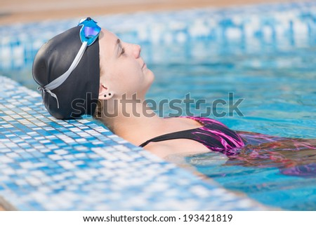 Portrait of a female swimmer wearing a swimming cap and goggles in blue water swimming pool. Sport woman.