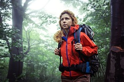 Portrait of a female trekker, wearing outdoor clothing and hiking backpack, trekking through deep, misty forest.