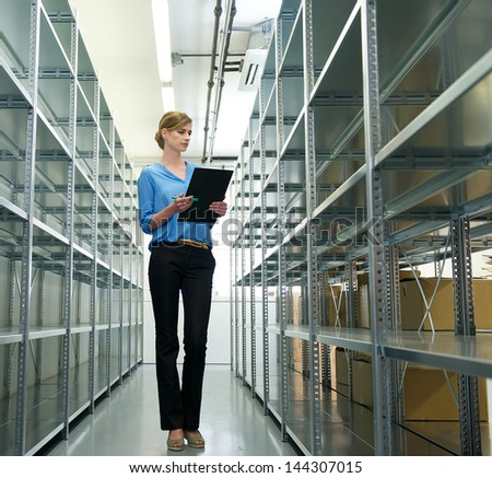 Portrait of a female worker with clipboard, organizing inventory and stock in warehouse
