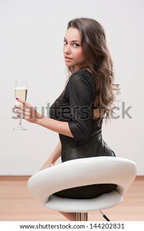 Portrait of a festive brunette beauty holding glass of champagne.
