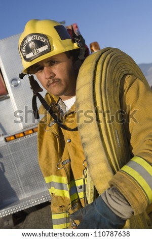 Portrait of a fire fighter carrying fire hose on shoulder - stock photo