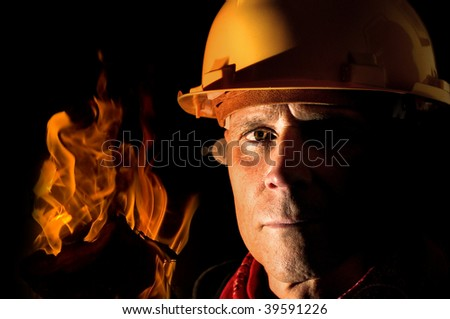 Portrait of a fireman isolated in black - stock photo