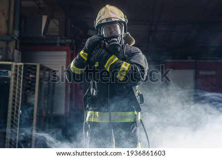 Portrait of a fireman wearing firefighter turnouts and helmet. Dark background with smoke and blue light.