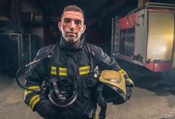 Portrait of a fireman wearing firefighter turnouts holding helmet ready for emergency service.