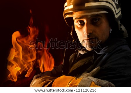 Portrait of a fireman with fire isolated in black
