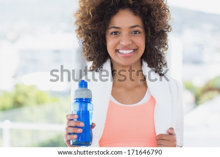Portrait of a fit young female holding water bottle at a bright gym