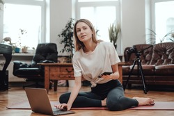 Portrait of a fitness girl with telephone using laptop which sits on mat around luxurious furniture and modern photocamera.