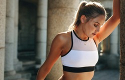 Portrait of a fitness woman relaxing during workout standing with eyes closed. Woman in fitness wear training holding a wall with sun flare in the background.