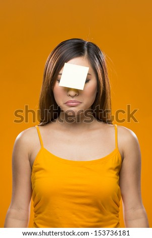 Portrait of a forgetful Asian Woman with a yellow sticky note on her forehead. Young fresh Chinese female model on bright orange background.