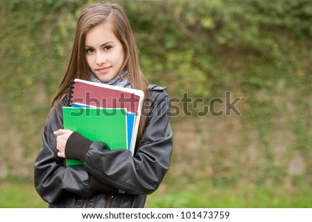 Portrait of a fresh young student girl in the park holding exercise books.