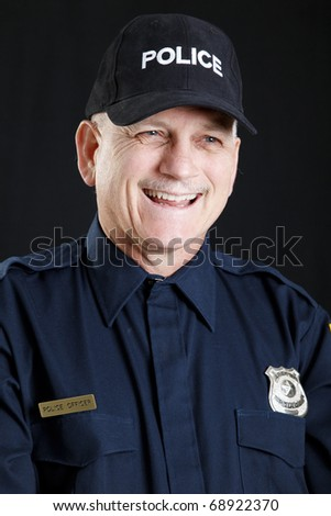 Portrait of a friendly, laughing policeman.  Studio shot against black background.
