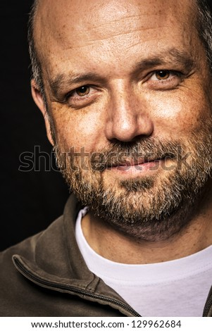 Portrait of a friendly looking, balding and unshaven man