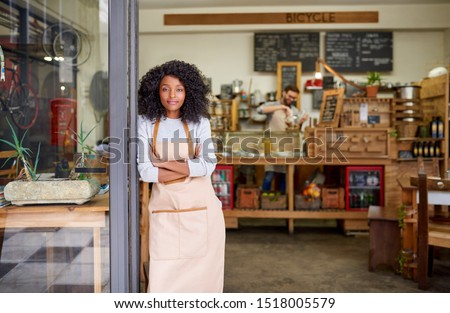 Portrait of a friendly young African American barista standing with her arms crossed at the door of a trendy cafe