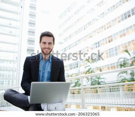 Portrait of a friendly young man using laptop inside building