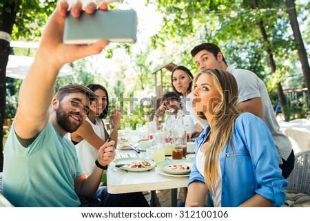 Portrait of a friends making selfie photo on smartphone in outdoor restaurant