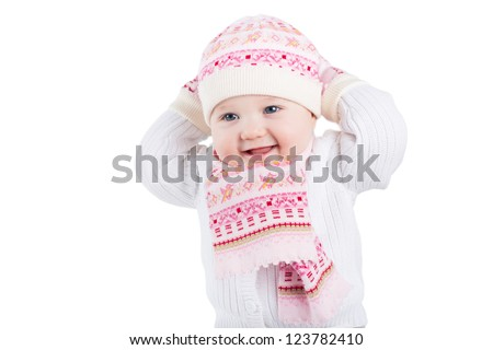 Stock Photo Portrait of a funny baby girl in a knitted hat, scarf and mitten, isolated on white
