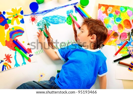 Portrait of a funny boy enjoying his painting. Education.