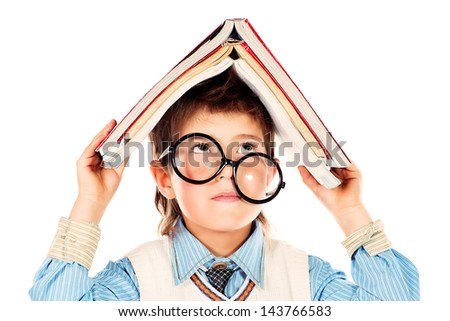 Portrait of a funny cute boy in huge glasses holding  books on his head. Isolated over white.