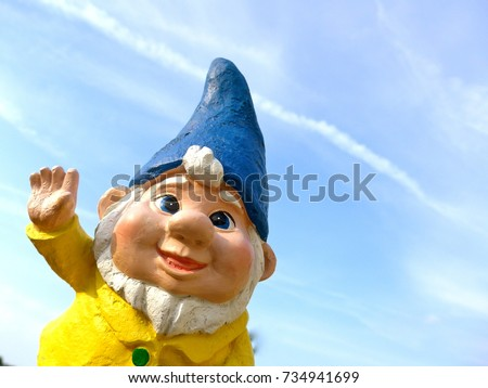 Portrait of a funny garden dwarf against a blue sky with little clouds