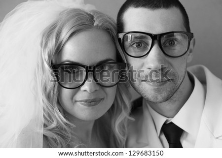 Portrait of a funny handsome hipster family (bride and groom) posing in trendy glasses together on their wedding day. daylight. studio shot