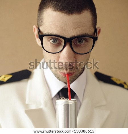 Portrait of a funny handsome hipster groom (dude) in trendy glasses drinking something from tin can through red plastic sipper. daylight. studio shot