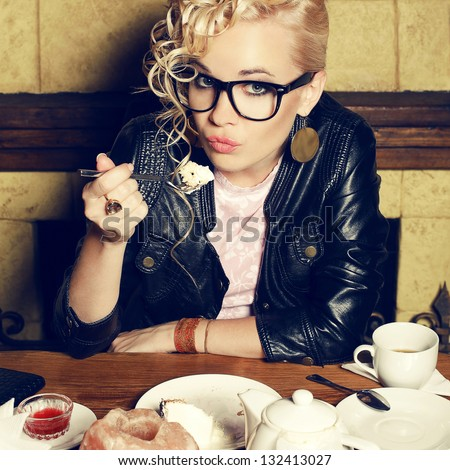 Portrait of a funny hipster blonde girl with great hairdo in trendy glasses and leather black jacket eating cake in the cafe. Close up. Indoor shot