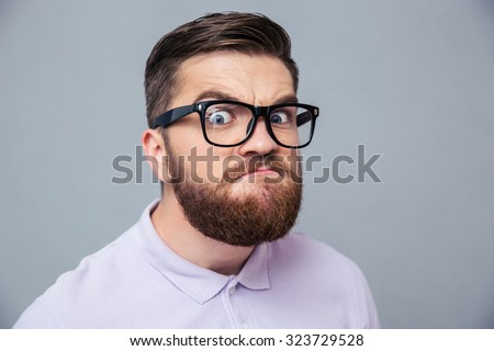 Portrait of a funny hipster man looking at camera over gray background Stock fotó ©