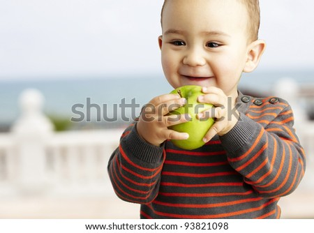 portrait of a funny kid holding a green apple against a shore background