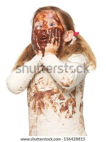 Portrait of a funny little girl with dirty face covered in chocolate isolated on white