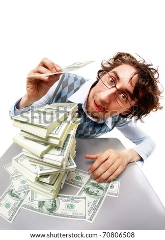 Portrait of a funny man with stacks of dollars