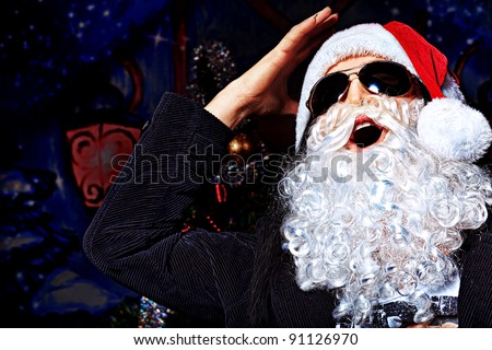 Portrait of a funny young man in Santa Claus costume making faces. Christmas.