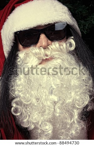 Portrait of a funny young man in Santa Claus hat and beard. Christmas.