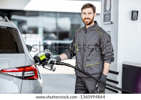 Portrait of a gas station worker in workwear refueling luxury car with gasoline at the station
