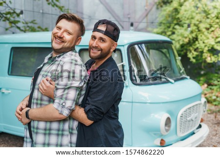 Portrait of a gay couple in front of an old-fashioned car van. Boyfriends hug and smile to the camera. #1574862220