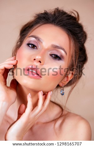 portrait of a gentle, refined woman who look into the camera and gently touches her face with her fingers #1298165707